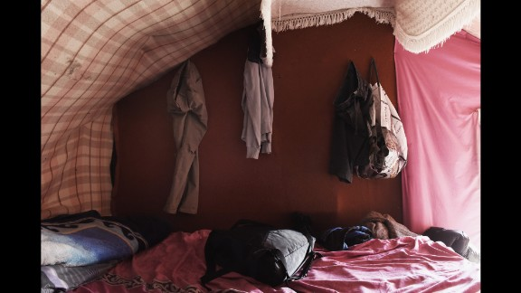 """The home of Sami, a refugee living in the """"The Jungle,"""" is pictured in August 2015. Sami, who has lived in the camp for two months, said: """"We made this house from blankets and wood and then covered it in plastic to keep the rain out. It rains often in France. I think it will rain often when I am in England, too."""""""