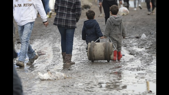 """Two young boys walk in the mud inside """"The Jungle"""" in December 2015."""