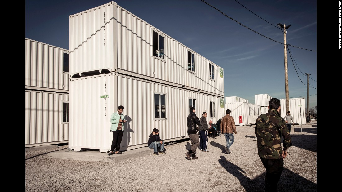 "Migrants walk past housing containers in ""The Jungle"" on Tuesday, February 16."