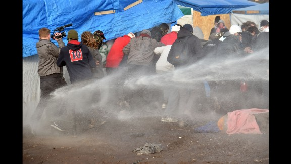 """Riot police spray water on migrants to disperse them during the dismantling of half of """"The Jungle"""" on February 29."""