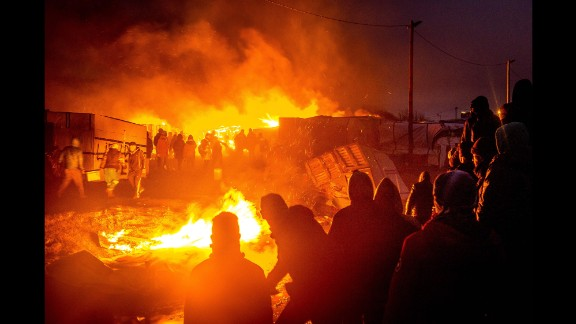 Migrants stand next to a burning shack in the camp on Tuesday, March 1.