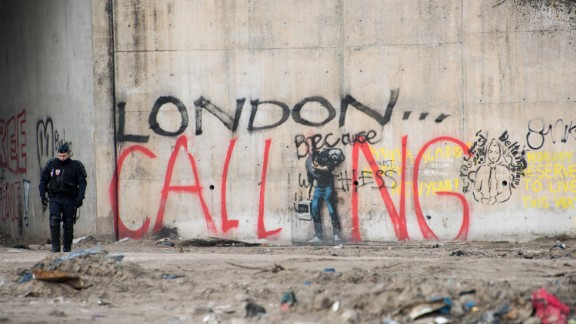 """A French riot policeman stands near graffiti during the dismantling of the southern part of """"The Jungle"""" migrant camp on Thursday, March 10. The graffiti reads """"London calling,"""" a reference to how the camp has become notorious for migrants and refugees trying to enter the UK illegally."""