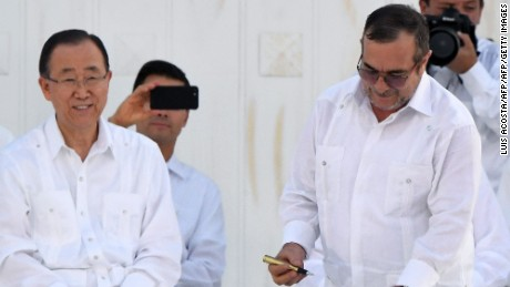 "The leader of the FARC, Rodrigo Londono (R) -- better known by his nom de guerre, Timoleon ""Timochenko"" Jimenez gets reads to sign the historic peace agreement between the Colombian government and the Revolutionary Armed Forces of Colombia (FARC), as Ecuador's President Rafael Correa (L) and UN Secretary General Ban Ki-moon look on and Mexican President Enrique Pena Nieto captures the moment with his cell-phone (C), in Cartagena, Colombia, on September 26, 2016  The Colombian government and the leftist FARC rebel force signed a historic peace accord to end a half-century conflict that has killed hundreds of thousands of people. Santos and ""Timochenko"" Jimenez, signed the deal at a ceremony in the Caribbean city of Cartagena, prompting loud cheers from the crowd which included numerous international dignitaries.  / AFP / Luis ACOSTA        (Photo credit should read LUIS ACOSTA/AFP/Getty Images)"