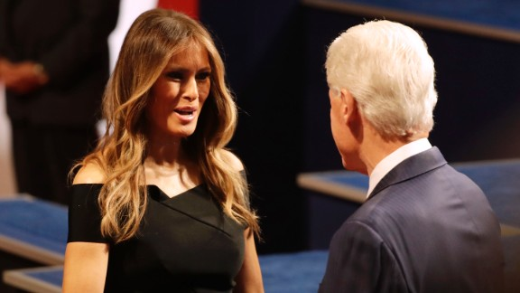 Trump's wife, Melania, shakes hands with Clinton's husband, former U.S. President Bill Clinton.