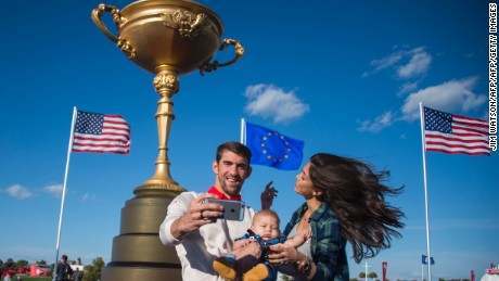 Olympic Gold Medalist Michael Phelps (L) and his fiancee Nicole Johnson (R) take a selfie with their son Boomer (C) at Hazeltine National Golf Course in Chaska, Minnesota on September 26, 2016, ahead of the 41st Ryder Cup.  / AFP / JIM WATSON        (Photo credit should read JIM WATSON/AFP/Getty Images)