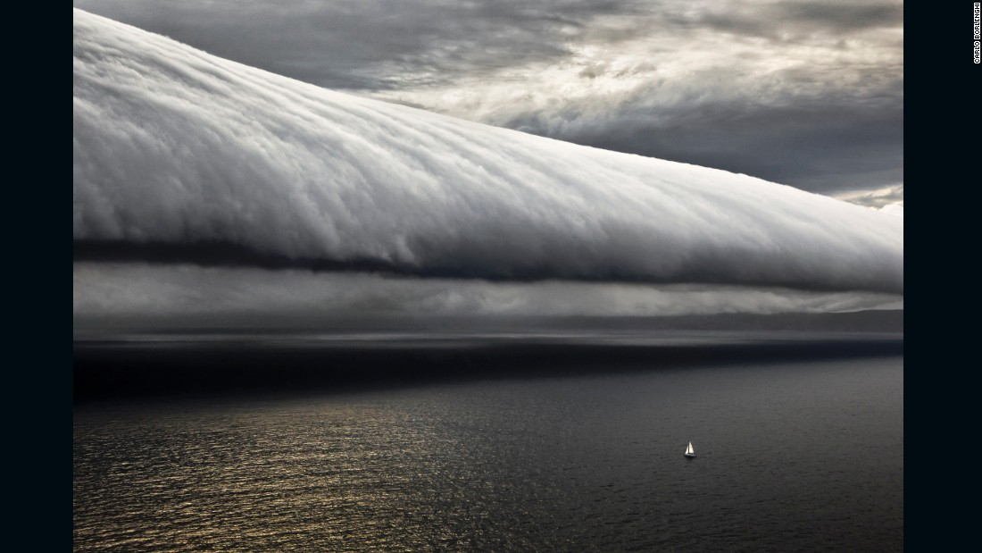 """The Rolex Sydney-Hobart Race, my favorite place to shoot.  And here is a good example of why, a very special weather event. The tiny boat is one of the last in the fleet from the 2010 edition of the race. And look at it, all alone out at sea with this giant cloud in its path.  Taken from the helicopter, away from the boat, this picture shows everything there is to know about being at sea in a race like this."""