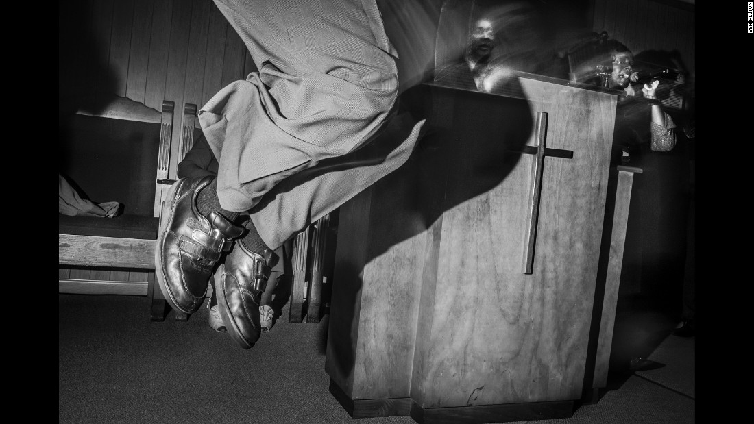An evangelist jumps for joy during a service. Helton shot photos with a handheld flash, creating images full of hard light, shadows and layers.