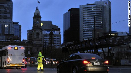 Police direct traffic around downtown Adelaide after the power network stopped working, creating a broad blackout across the city.