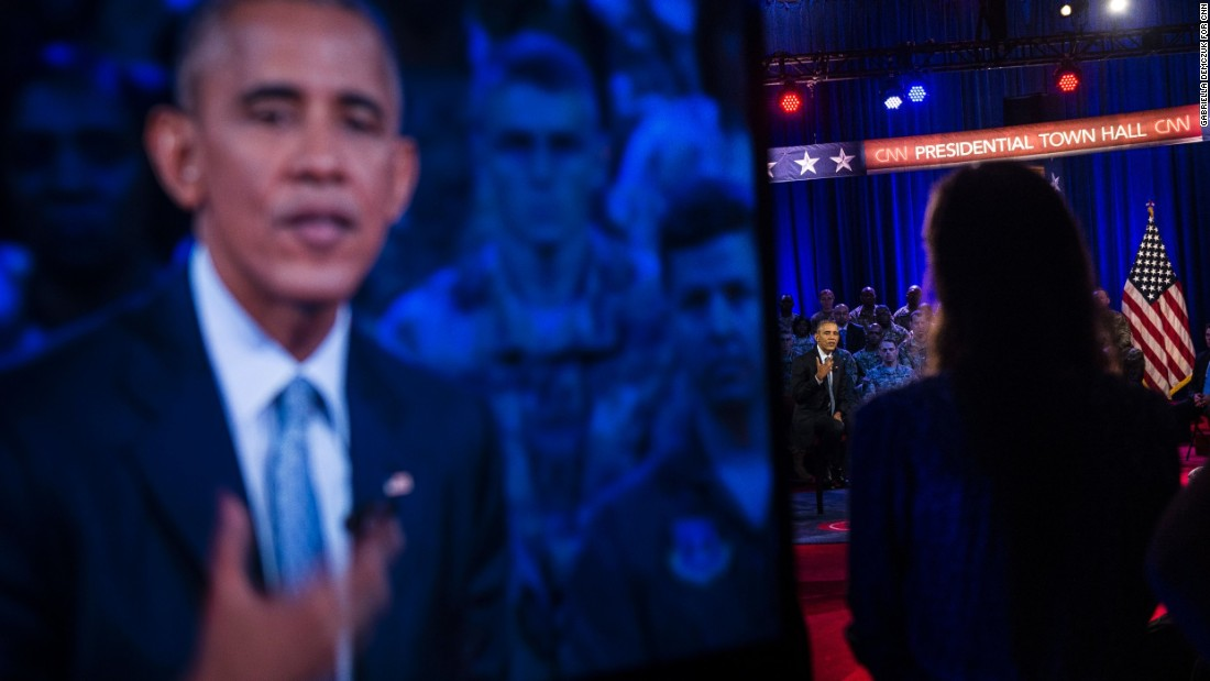 A television screen shows Obama answering a question during the event.