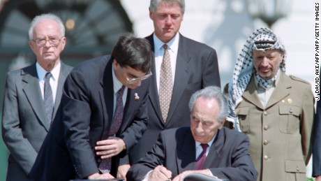 Shimon Peres signs the Oslo Accords in the White House while Yitzhak Rabin, President Bill Clinton and Yasser Arafat observe.