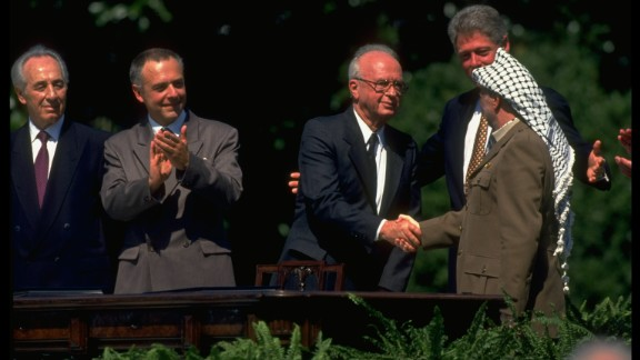 Shimon Peres (far left, then foreign minister) looks on as PLO Chairman Yasser Arafat shakes hands with Israeli Prime Minister Yitzak Rabin on the White House lawn.