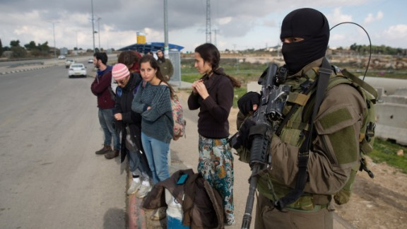 An Israeli soldier stands guard as Israeli settlers stand at a bus station in the West Bank.