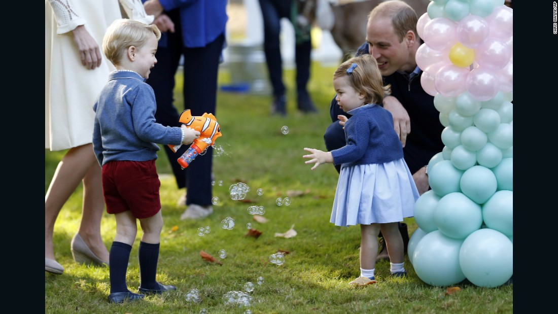 Prince George plays with a bubble gun near his sister, Princess Charlotte, and his dad, Prince William, on September 29.