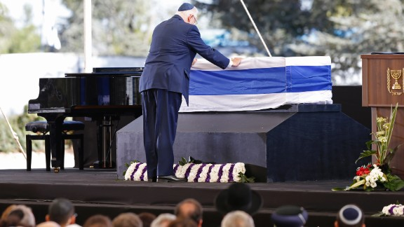 """Israeli President Reuven Rivlin touches Peres' coffin. In his tribute, Rivlin said that Peres was """"the man of whom we thought time could never stop."""""""