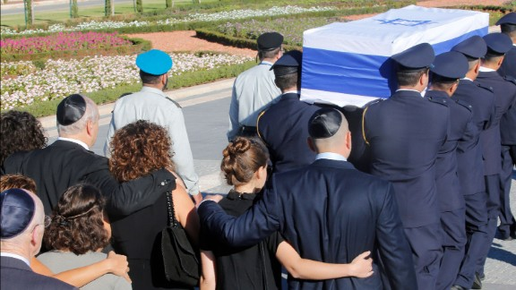 Family members walk behind Peres