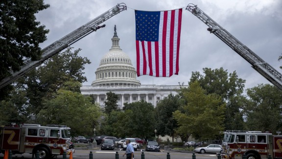 An American flag is suspended from the ladders of two fire trucks in Washington on Wednesday, September 28. Congress had just voted to override a presidential veto on legislation that would allow the families of 9/11 victims to sue the government of Saudi Arabia.