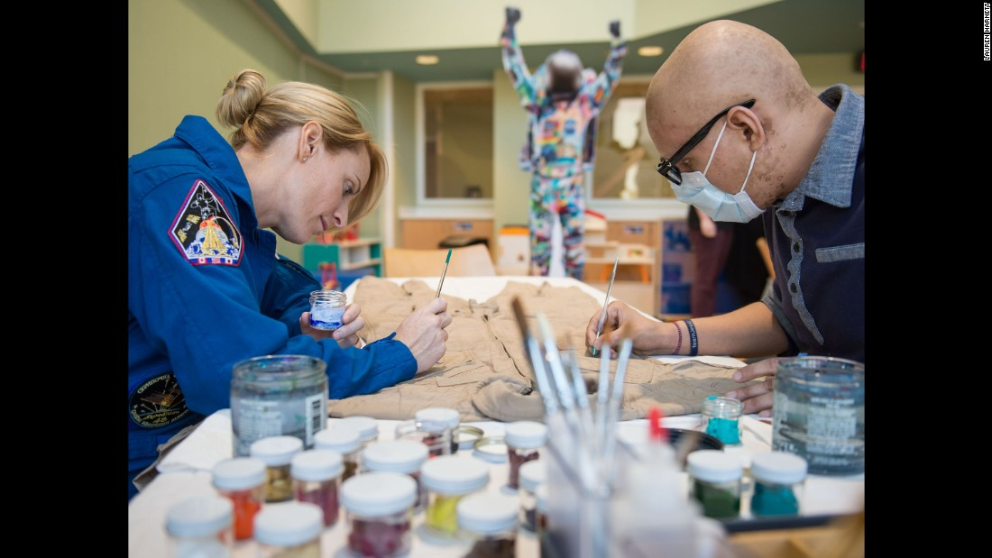 Rubins and pediatric cancer patient David Olazaba painted the first brush strokes on the Courage flight suit.