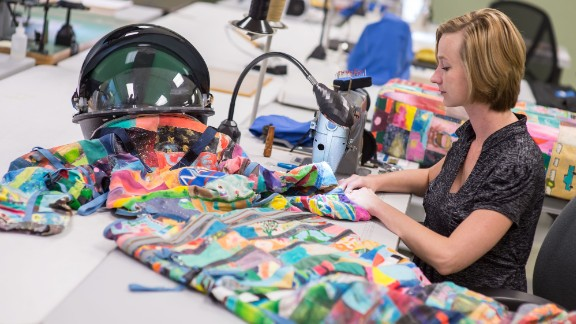 Whitney Lowery, a NASA space suit technician with ILC Dover, works on sewing art pieces to build the children