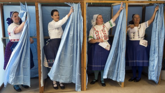 Hungarian women wearing traditional clothes cast their ballot at a polling station Sunday in Budapest.