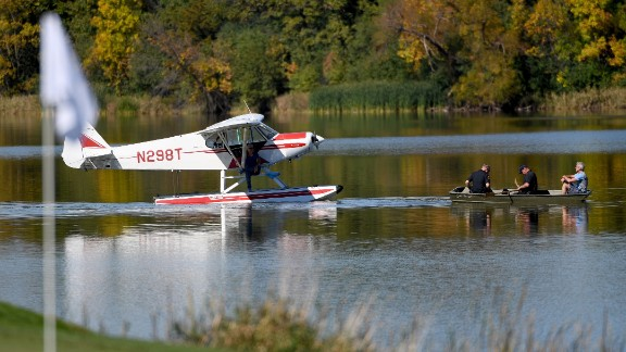 Police pick up an occupant of a sea plane that landed near the seventh green during singles matches.