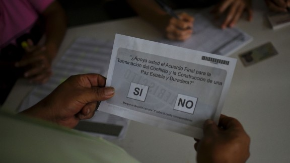 A Colombian receives a ballot before voting in the October referendum.