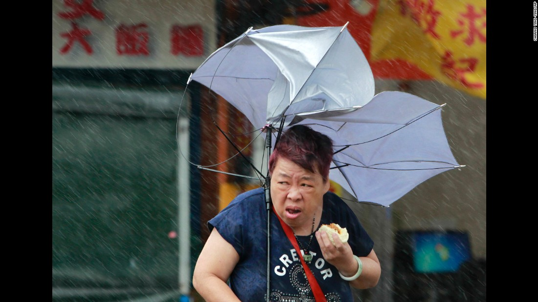"A woman in Taipei, Taiwan, struggles with her umbrella as she eats food on Tuesday, September 27. Typhoon Megi brought powerful winds to the island before <a href=""http://www.cnn.com/2016/09/26/asia/typhoon-megi-taiwan-weather/index.html"" target=""_blank"">making landfall in mainland China.</a>"