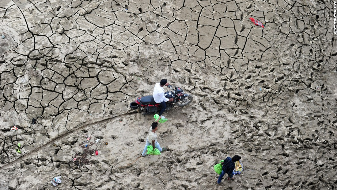 People cross a marshy area on the bank of the river Yamuna after floodwaters receded in Allahabad, India, on Tuesday, September 13.