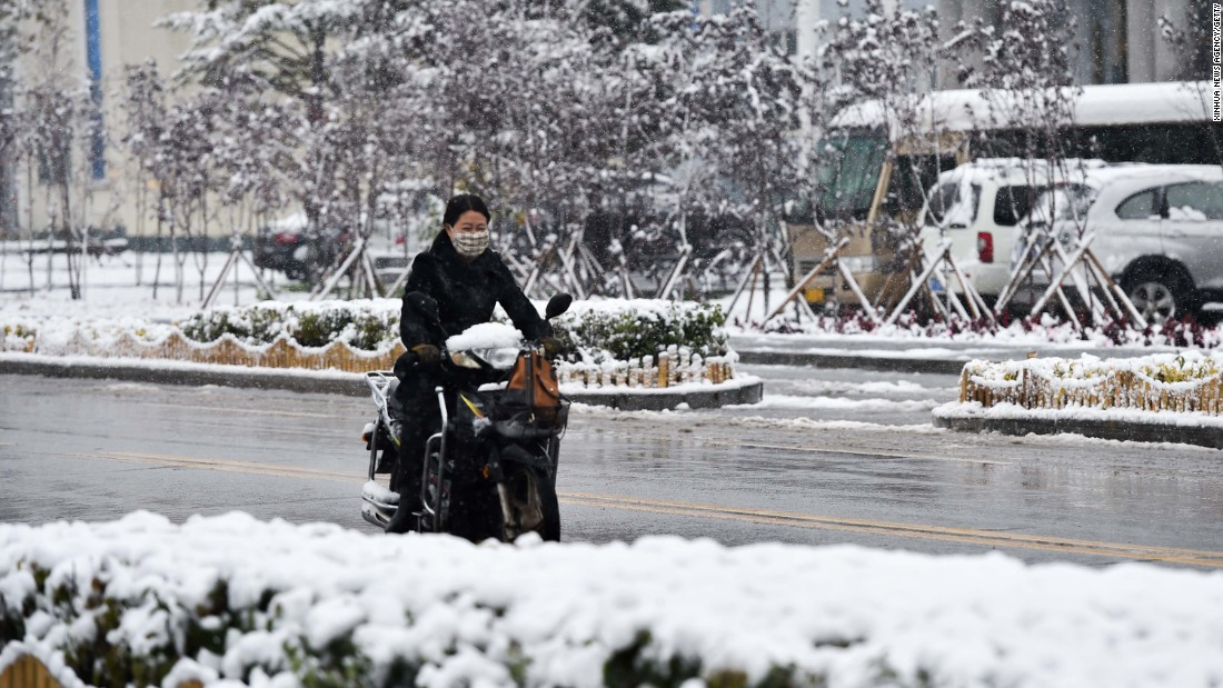 A woman rides through Arxan, China, after its first snowfall of the season on Monday, September 27.