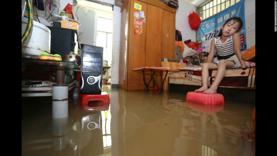 "A girl sits on her bed after heavy rain caused by <a href=""http://www.cnn.com/2016/09/12/asia/typhoon-meranti-weather/"" target=""_blank"">Typhoon Meranti</a> flooded her home in Jinjiang, China, on Thursday, September 15."