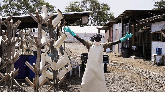 """There were celebrations when the West African Ebola epidemic was declared """"no longer an emergency"""" in March 2016. But while the outbreak is over, Ebola is is still out there. Pictured, a Liberian worker dismantling shelters in a treatment center in March 2015."""