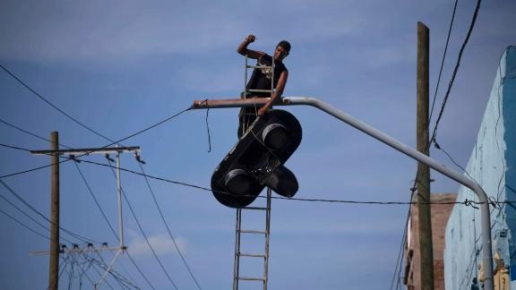 A worker dismantles a traffic light in Santiago before Hurricane Matthew struck Cuba.