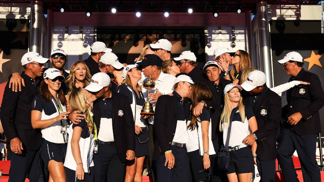 "Golfer Rickie Fowler shrugs as his U.S. teammates kiss their wives and girlfriends <a href=""http://www.cnn.com/2016/10/03/golf/ryder-cup-2016-reactions-obama-arnold-palmer/index.html"" target=""_blank"">during a team photo</a> on Sunday, October 2. The team had just won the Ryder Cup."