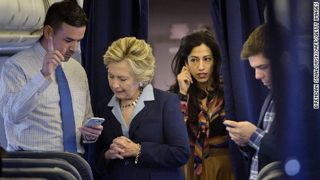 Hillary Clinton (2L) looks at national press secretary Brian Fallon's (L) smart phone while on her plane with aid Huma Abedin (2R) and traveling press secretary Nick Merrill (R) at Westchester County Airport October 3, 2016 in White Plains, New York.