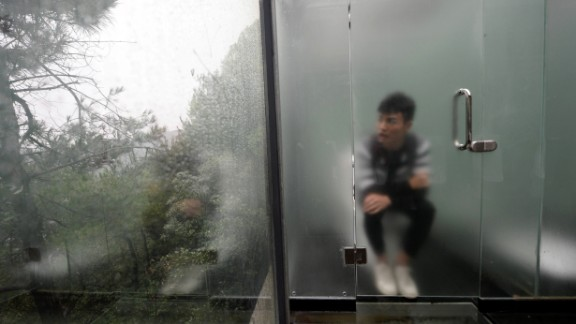 This photo taken on September 29, 2016 shows a tourist visiting a glass-walled public toilet in Shiyan Lake scenic area in Changsha, central China's Hunan province. The glass toilet was open for the public from September 29.