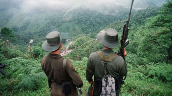 "FLORENCIA, COLOMBIA:  Two armed soldiers belonging to the Revolutionry Armed Forces of Colombia (FARC) monitor the Berlin pass, 07 March, near Florencia, in the  southern Caqueta province of Colombia, where cars are prevented from going through after the rebels decreed 06 March a ban on ""travel on roads and waterways for six days"". The rebels try to dissuade voters from casting their ballots in the 08 March elections for congress. According to the rebels, the elections 08 March are illegitimate because the left has been forced out of national politics, following the murder over the past years of thousands of Colombia"