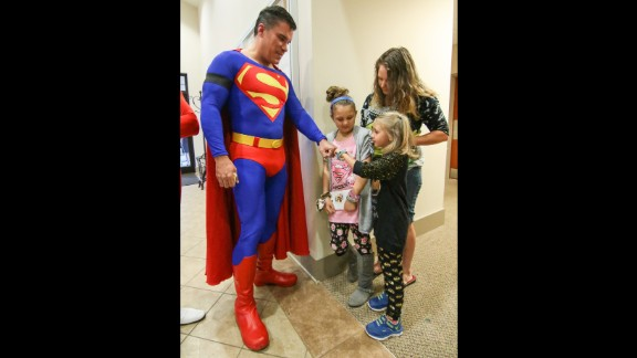 Zowie Sanders gives a fist bump to John Suber of Greenville, dressed as Superman, at Tuesday's visitation.