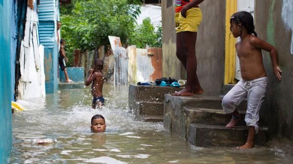 Children swim in a flooded neighborhood of Santo Domingo on October 4.