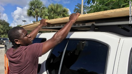 Texroy Spence, of Deerfield Beach, Florida, loads plywood onto his car at the Home Depot on Tuesday.