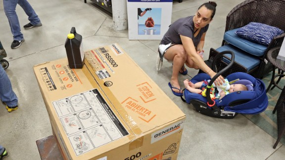 Anita Baranyi feeds her baby while keeping an eye on the generator she intends to purchase from a home-improvement store in Oakland Park, Florida, on October 4.