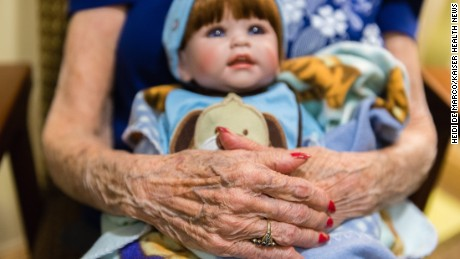 Vivian Guzofsky, 88, holds a baby at Sunrise Senior Living in Beverly Hills, California, on August 2, 2016. Some nursing homes are using a technique called doll therapy to ease anxiety among their residents with dementia.  (Heidi de Marco/KHN)