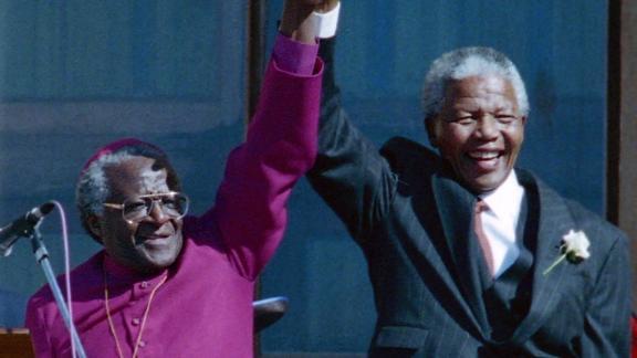 Tutu stands with Mandela after Mandela was elected president in 1994.