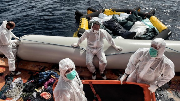 Members of Proactiva Open Arms move the bodies of 29 migrants to a life boat. How to help the ongoing migrant crisis