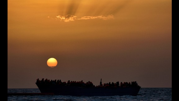 Migrants wait to be rescued as they drift at sunset in the Mediterranean Sea.