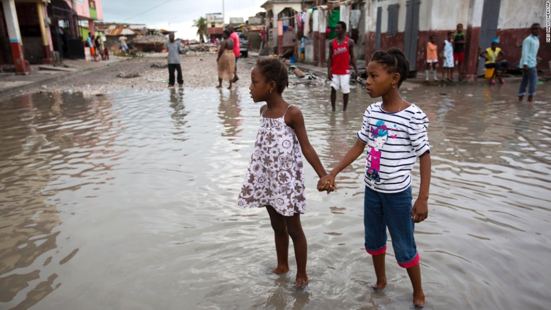 Girls wade through a flooded street in Les Cayes on October 6.
