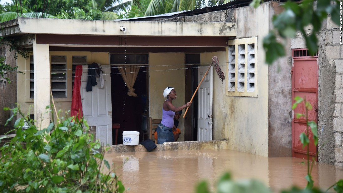 A woman cleans her flooded home following the overflowing of La Rouyonne River on October 5 in Leogane. Residents could face risks from standing water. Haiti is still recovering from a cholera outbreak after the devastating 2010 earthquake.