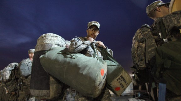KUWAIT CITY, KUWAIT - DECEMBER 15:  U.S. Army Specialist Christopher Riveria from West Palm Beach, Florida of the 2-82 Field Artillery, 3rd Brigade, 1st Cavalry Division, carries his bags to customs as he prepares to fly home to Fort Hood, Texas after being one of the last American combat units to exit from Iraq on December 15, 2011 at Camp Virginia, near Kuwait City, Kuwait. Today the U.S. military formally ended its mission in Iraq after eight years of war and the overthrow of Saddam Hussein.  (Photo by Joe Raedle/Getty Images,)