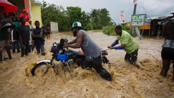 Men push a motorbike through a flooded street in Leogane on October 5. More than 300,000 people are in shelters across the country, the United Nations said.