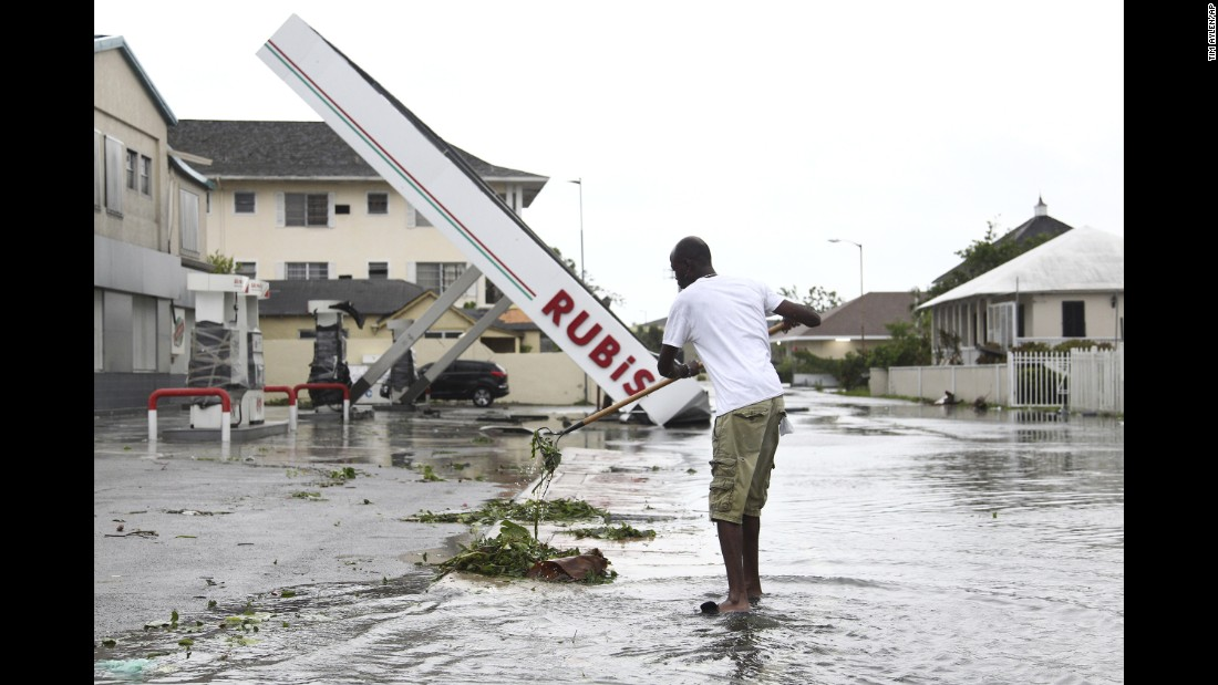 A man rakes up debris from a storm drain as he begins cleanup near a damaged gas station in Nassau on October 6.