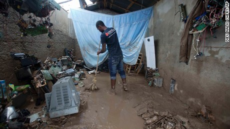 A man cleans his destroyed office, which is filled with thick mud.