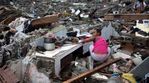 A woman searches amid the rubble of her home destroyed by Hurricane Matthew in Baracoa, Cuba, Wednesday, Oct. 5.